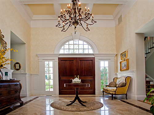 photo of grand foyer with custom stained doors, designer wallcoverings and painted woodwork and ceiliing