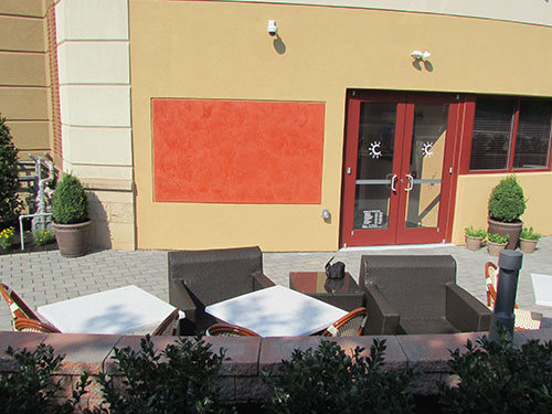 photo of terra cotta venetian plaster on exterior wall of the terrace at Carmel Kitchen and Wine Bar created by the Old Village Design Studio