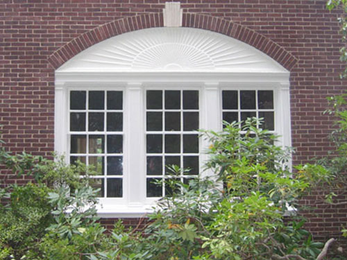 Detail of window under archway with sunrise millwork