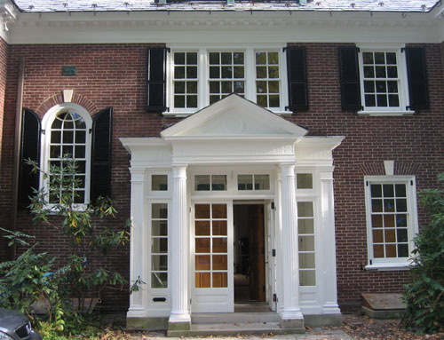 photo of exterior of brick mansion with center portico with glass pane doors, side lights and transoms painted in white, arched window on left, two windows on top and one to the right