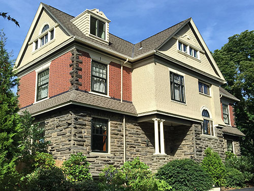 photo of Victorian home in Chestnut Hill, PA with cedar shake siding and arched windows. Old Village Master Painters repainted the cedar shakes and window trim to match old photos