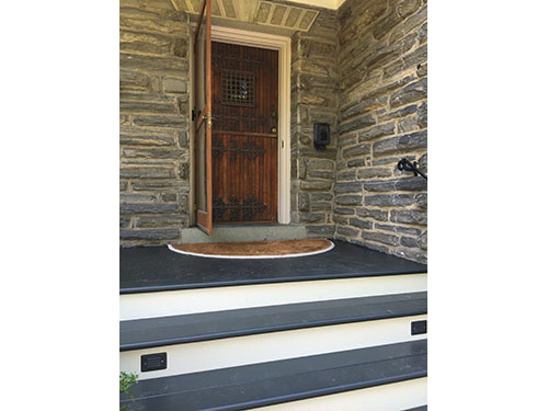 photo of wooden stairs and deck leading to door in stone wall