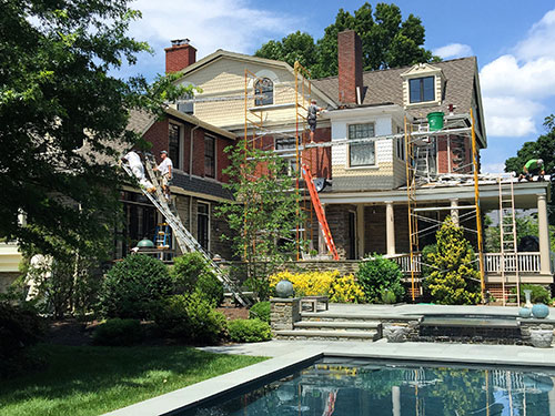 photo of rear of Victorian home in Chestnut with pool in foreground in process of being painted