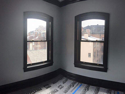 photo of 2 windows and wood word painted glossy black against white walls and protective matting on floor