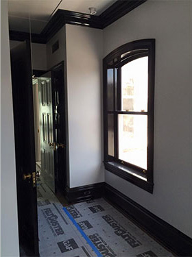 photo of hallway with white walls, window, wood work and door on right and door on left finished in high gloss black.