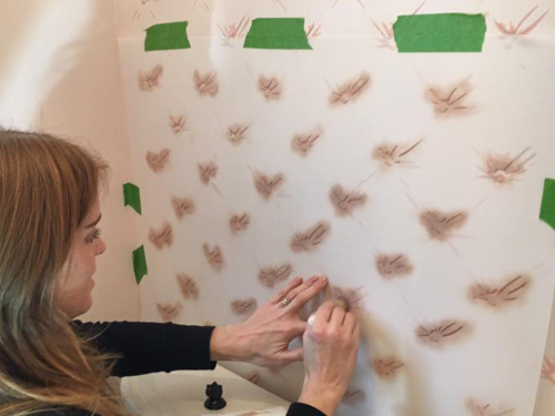 photo of Emilie Stulb Magowan hand-painting design on wall to reproduce damaged wallpaper