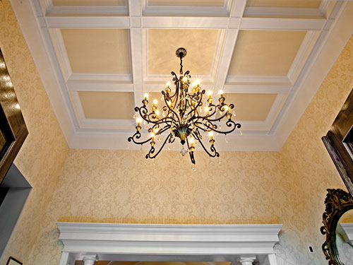 photo of Coffered Ceiling and Chandelier Detail with beautiful golden wallcoverings