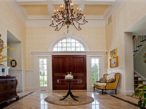 photo of Grand Foyer with great chandelier hanging from coffered ceiling, custom stained french doors with side lights and below semi-circular window