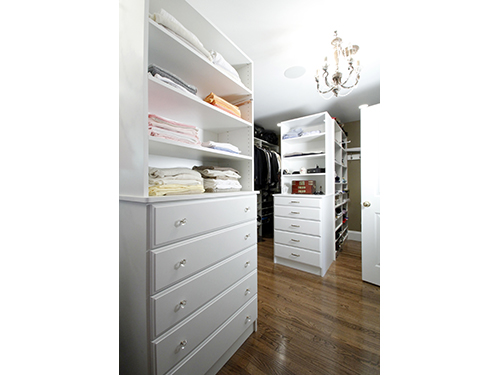 photo of walk-in closet with white shelving and cabinets