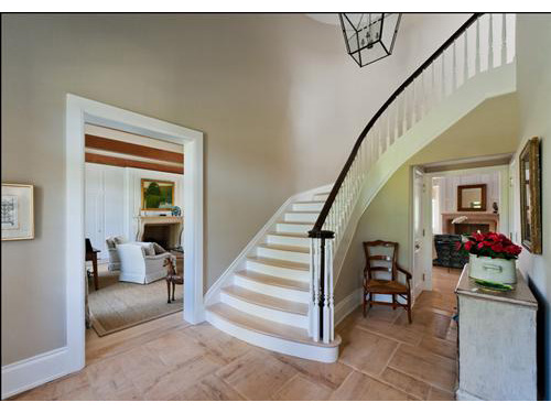 photo of foyer with doorway to left and dramatic curved staircase in center.