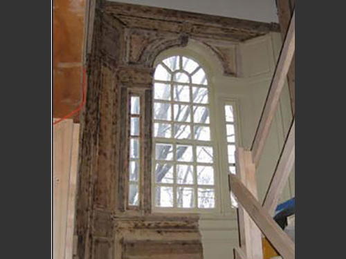 photo of ornate multi-paned arched window interior half way in process of lead paint removal