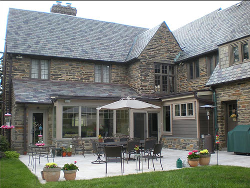photo of rear of stone home with patio and furniture
