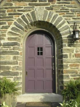 photo of plum painted door with lavender trim, with 4 pane window.  Stone step in front and set into a stone roman arhc