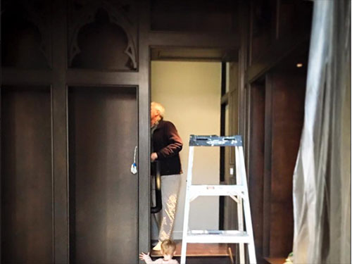 photo of wood paneled walls with doorway - ladder in doorway and past ladder man inspecting panels