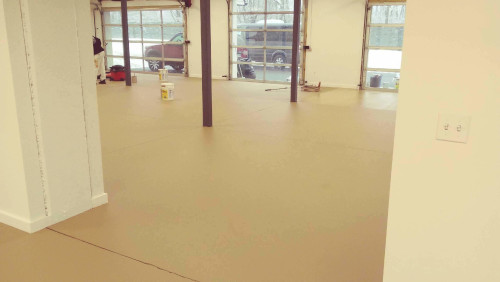 Garage with polymer epoxy floor in light yellow with three garage doors in center back