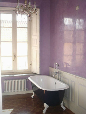photo of bathroom with claw foot tub painted dark blue, white wainscotting, lavender venetian plaster walls