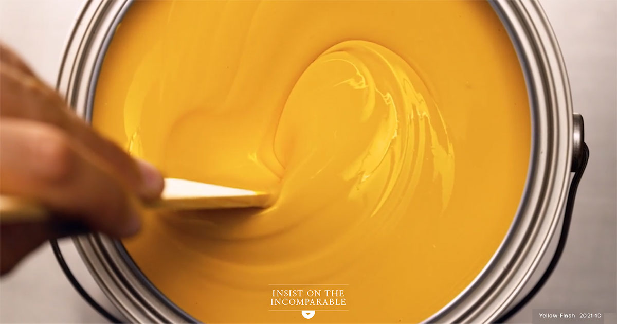 photo Benjamin Moore yellow flash paint being stirred in a paint can