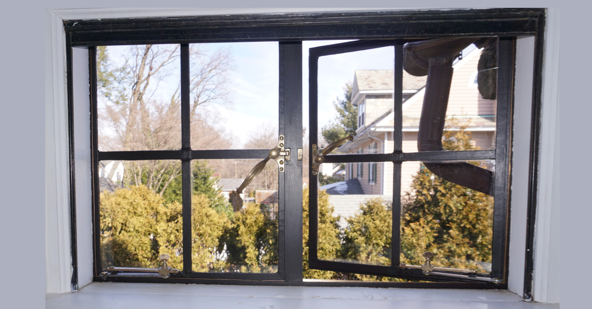 photo of casement windows with one open.  black finish and brass handles
