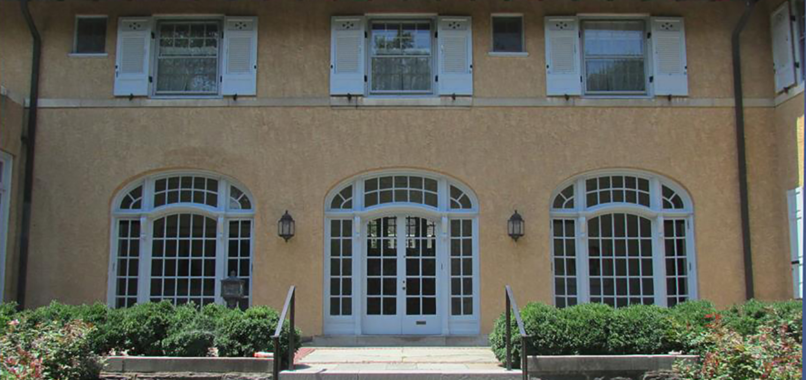 photo of 3 doors with palladium arches with 41 window panes each with sash windows on second floor