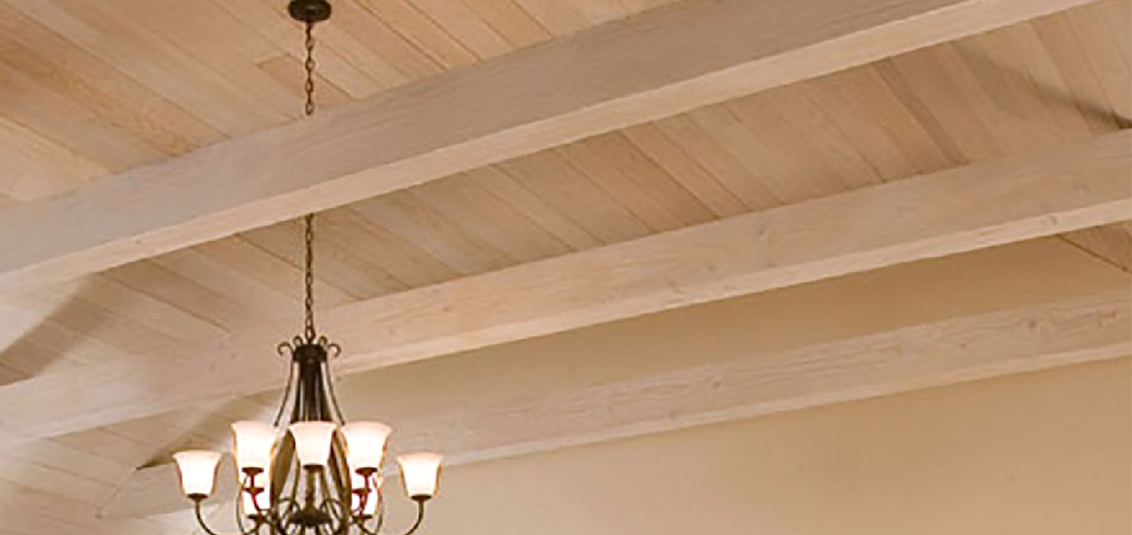 photo of chandelier hanging from ceiling of exposed beams and boards with light pickling color