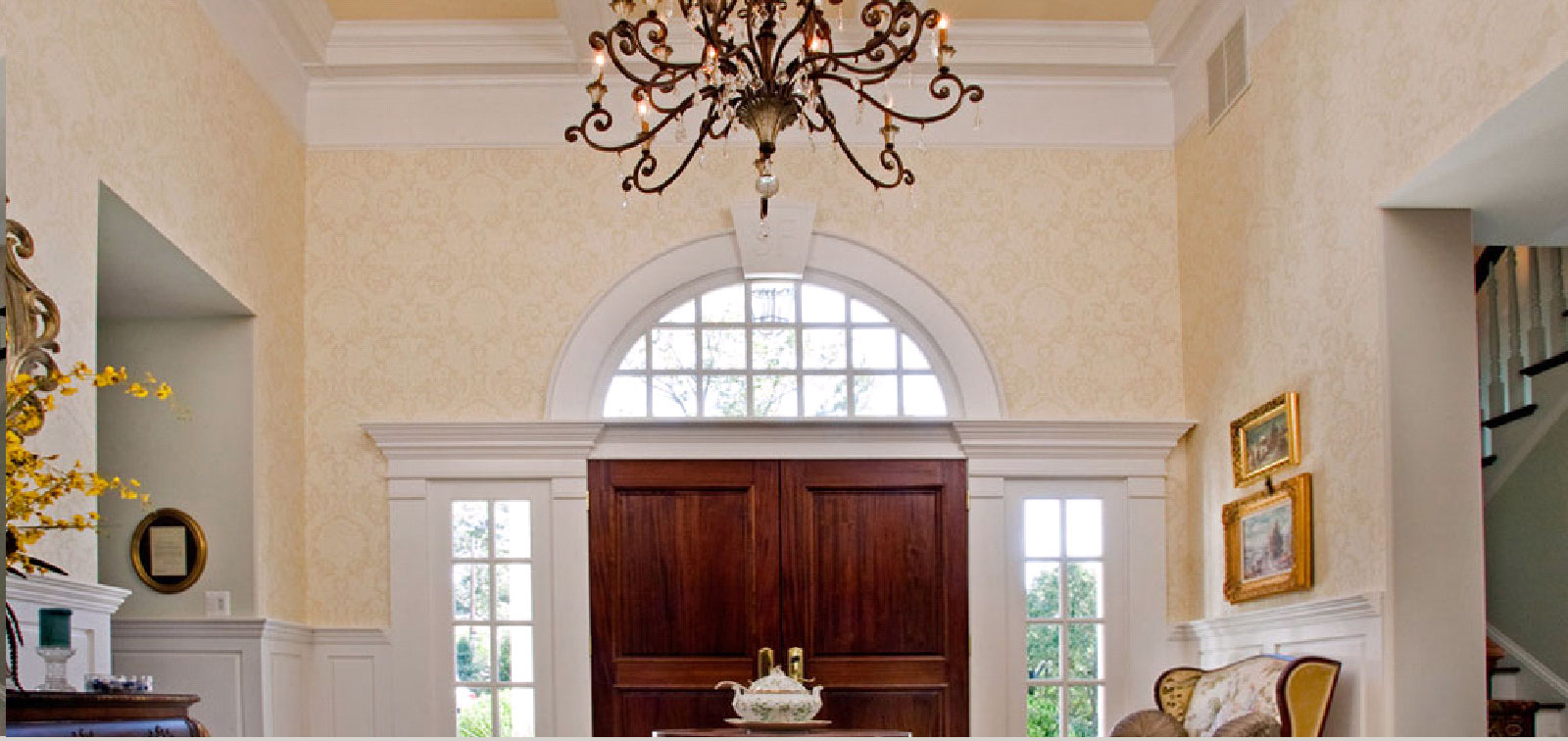 photo of great room foyer with chandelier hanging from coffered ceiling in front of palladium windows around custom finished doors