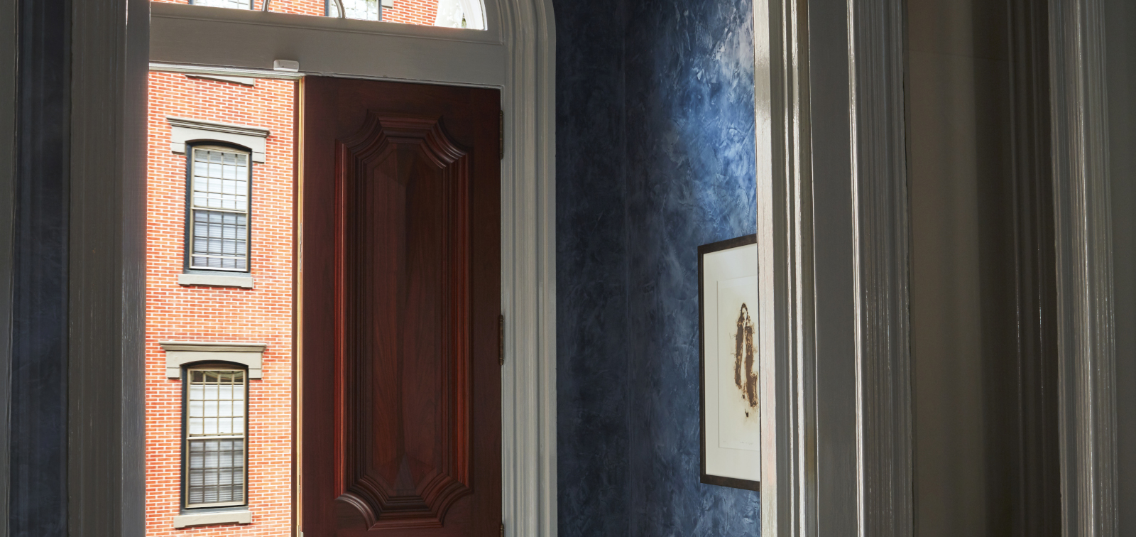 photo of foyer showing white woodwork around stained door to left and blue venetian plaster to the right