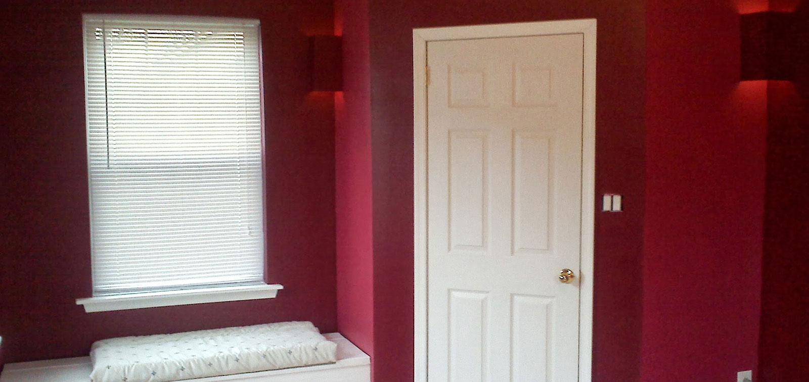 photo of bedroom showing beautiful deep red against classic white closets and moldings