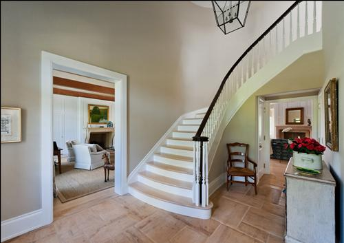 photo of foyer with curved staircase, wall papered walls, dark walnut finish on hand rail
