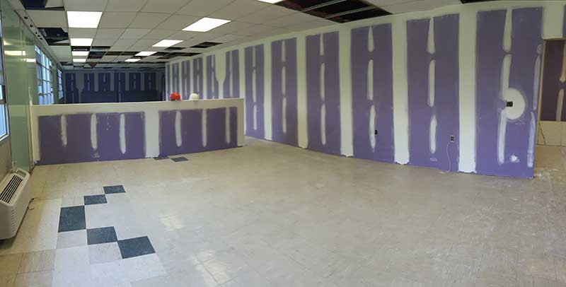 photo of classroom with unpainted drywall and linoleum floors